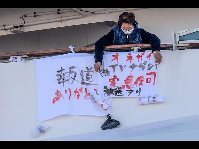 """Пассажир вешает баннер с надписью """"Спасибо, что сообщили об этом"""", слева от которого баннер с надписью """"Пожалуйста, передайте это по телевизору"""" на круизном лайнере Diamond Princess. 10 февраля 2020 года, Иокогама, Япония"""