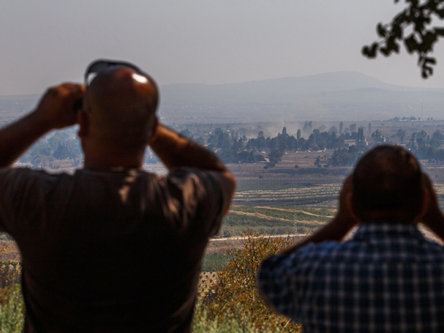 Израильтяне наблюдают за боем на территории Сирии в районе Кунейтра
