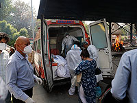 Медицинские работники выгружают тела шести человек, умерших от COVID-19, для кремации в Нью-Дели, Индия. Апрель 2021 года