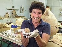 Археолог Алла Нагорски держит куриное яйцо, которому тысяча лет