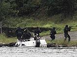 Около 18:20. Полицейские из отряда спецназначения окружают на острове Утойя вооруженного мужчину